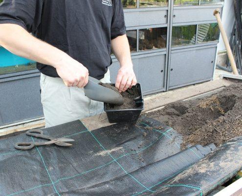 Vul het mandje met aarde en knip het resterende worteldoek weg.